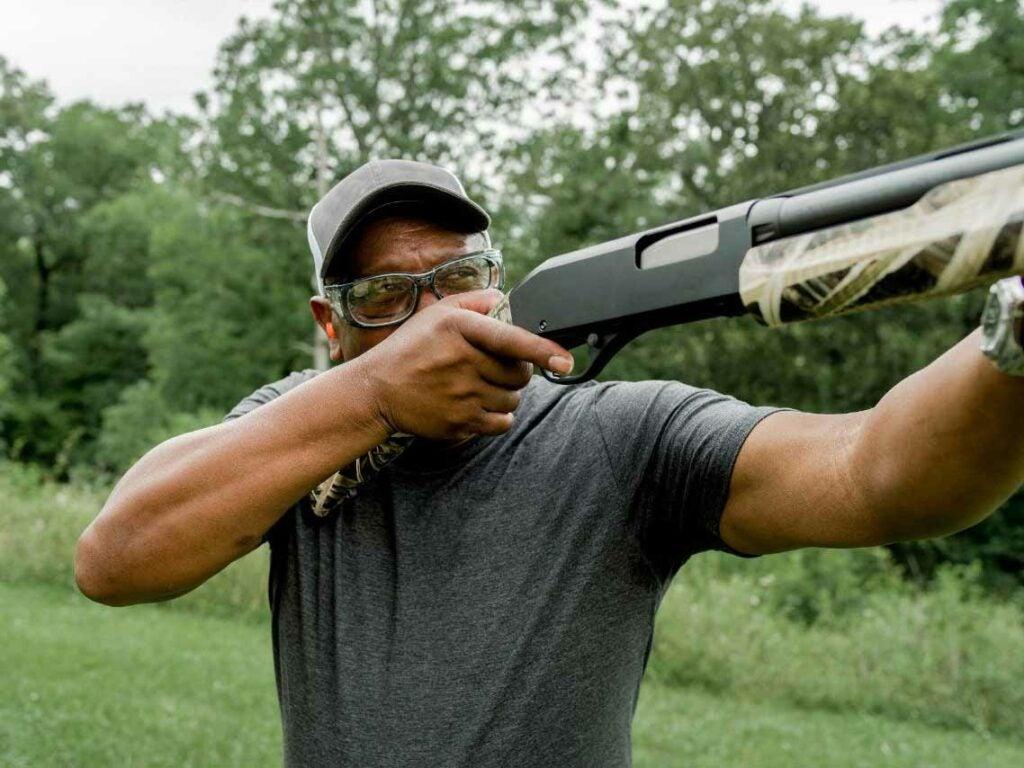 A man lifts and aims a shotgun in a shooting range.