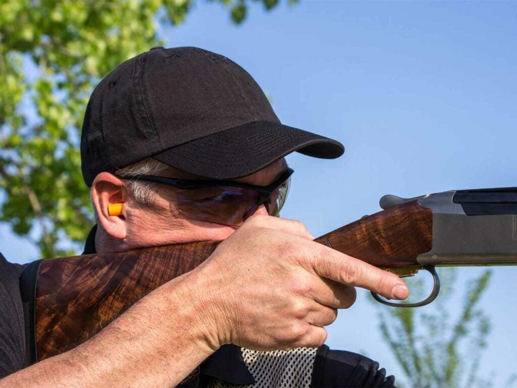 Man aiming a shotgun in a field.