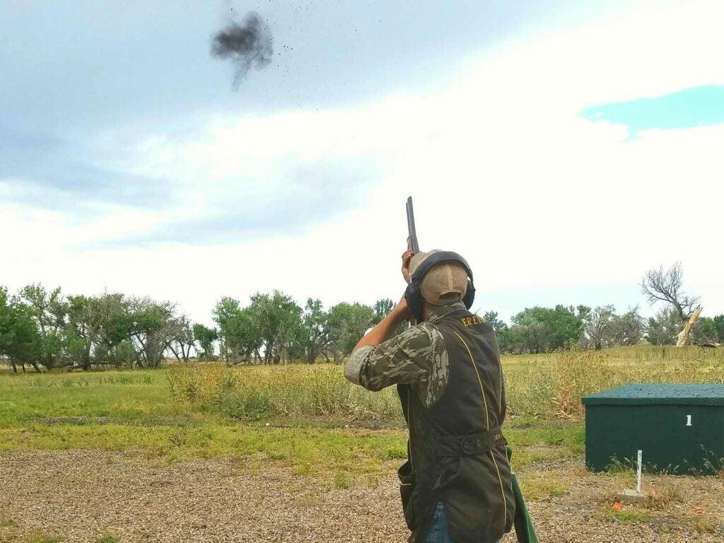 Man in a camo shooting skeet in a field.