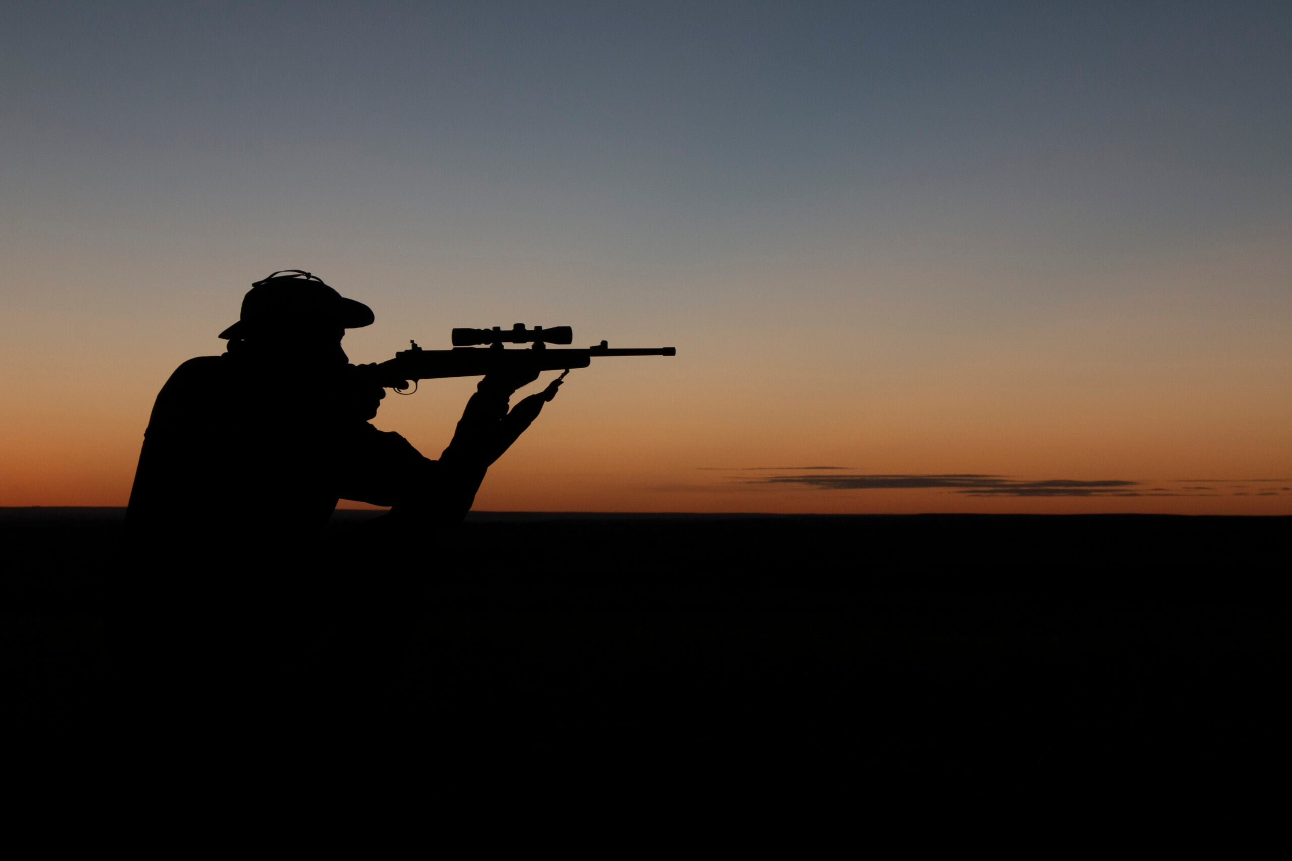 Silhouette of a man aiming a rifle against the sunset.