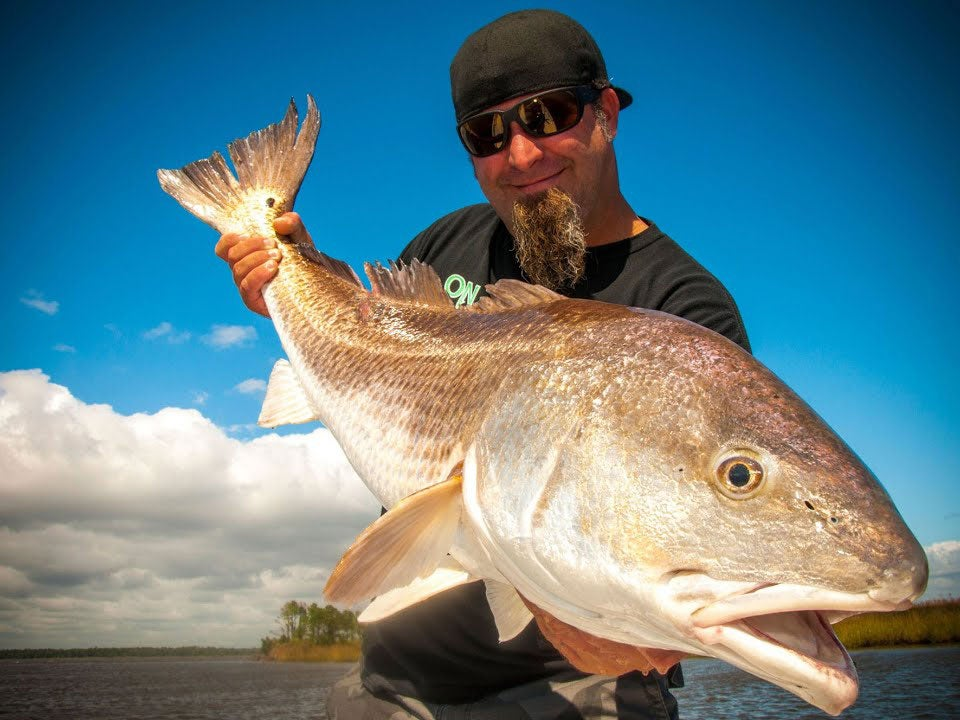 An angler holding up a large redfish.