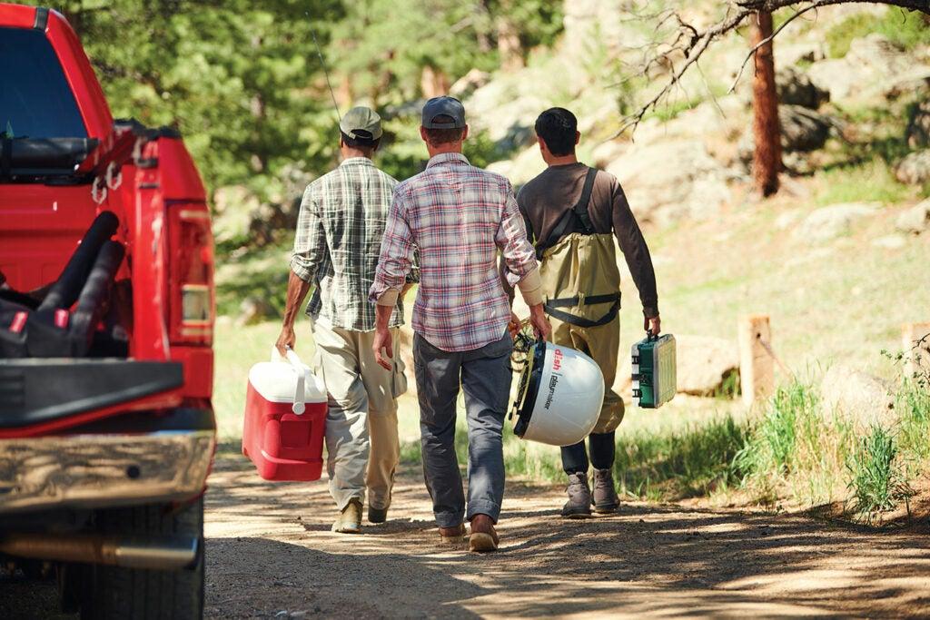 Three men walking with camping supplies.