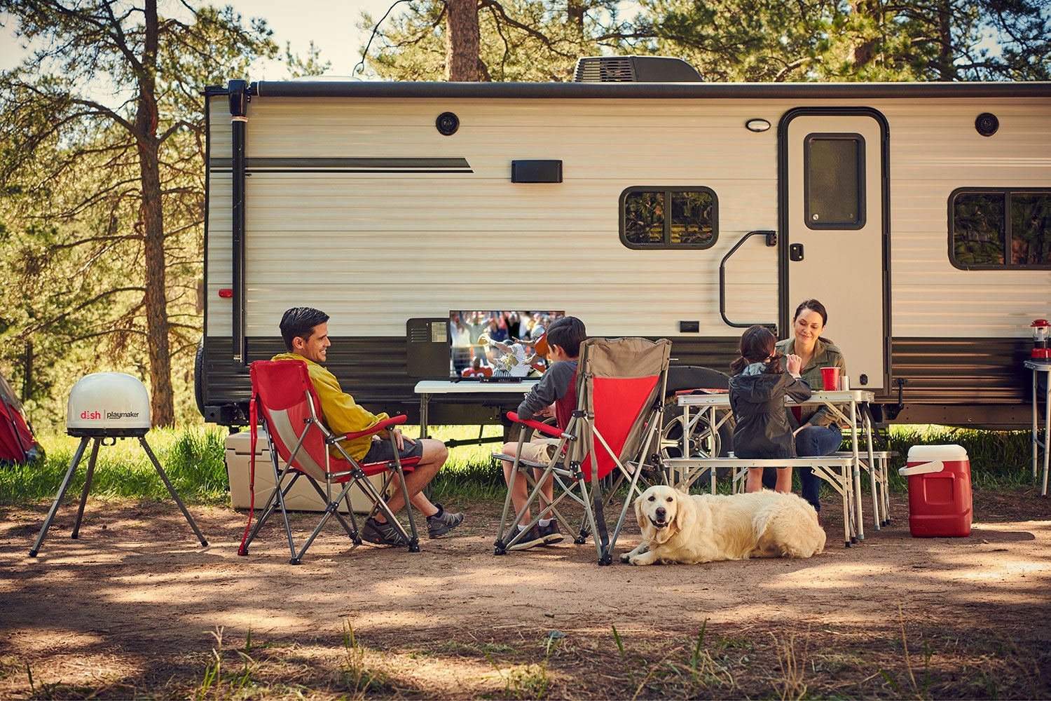 A group of campers sitting outside of an RV.