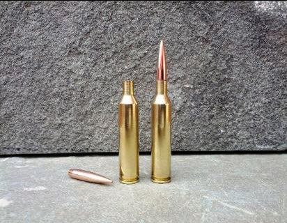 Two rifle cartridges on a stone floor.