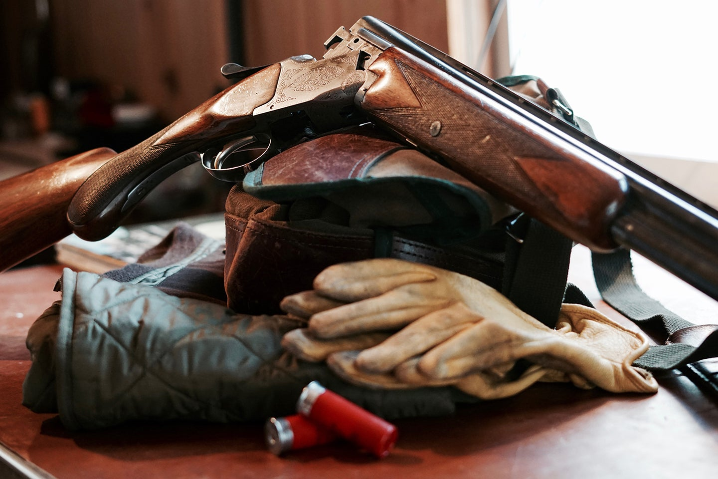 A Browning shotgun and hunting gear on a table.
