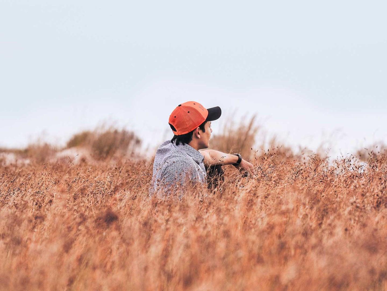 man sitting in a field wearing an orange hat