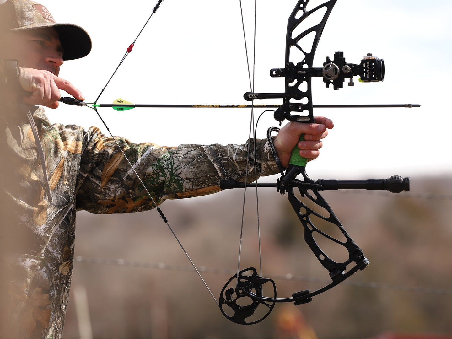 A bowhunter drawing back on a compound bow.
