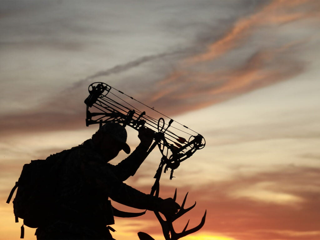 Silhouette of a bowhunter against the sunset.