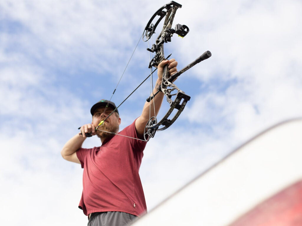 Bowhunter aiming a compound bow and drawing back.