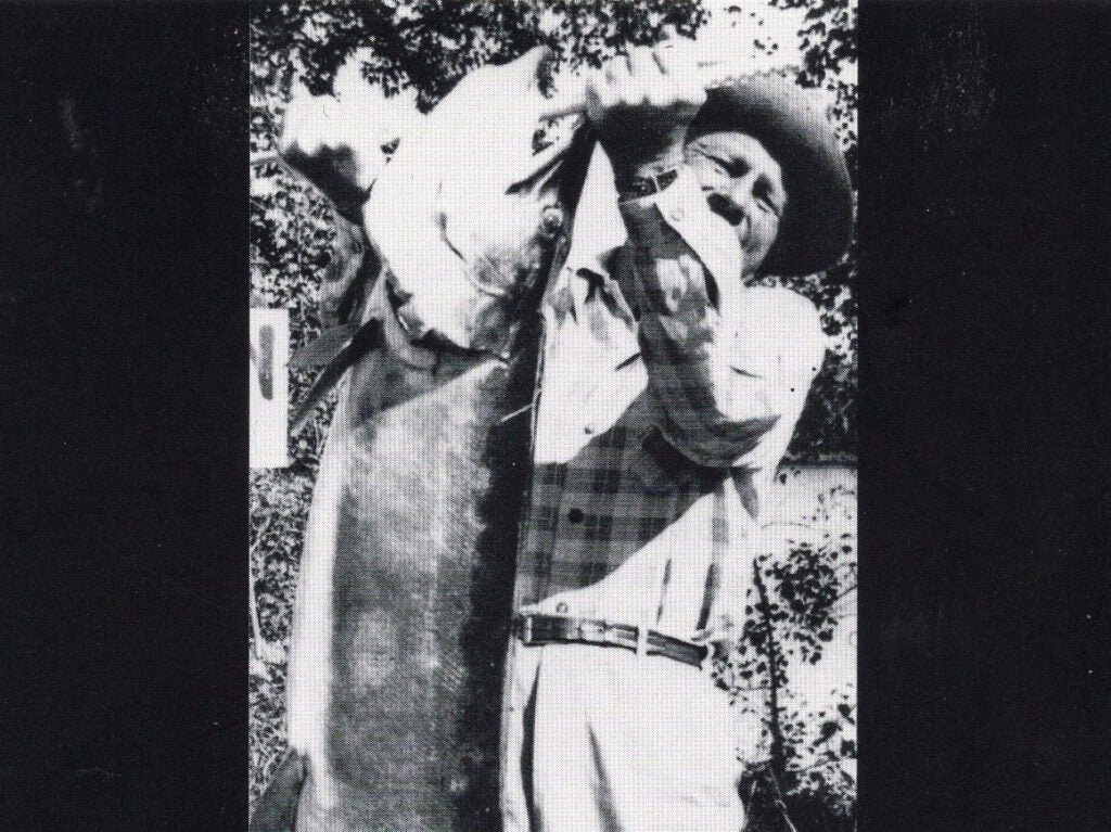 A black and white photo of a man holding up a large muskie fish.