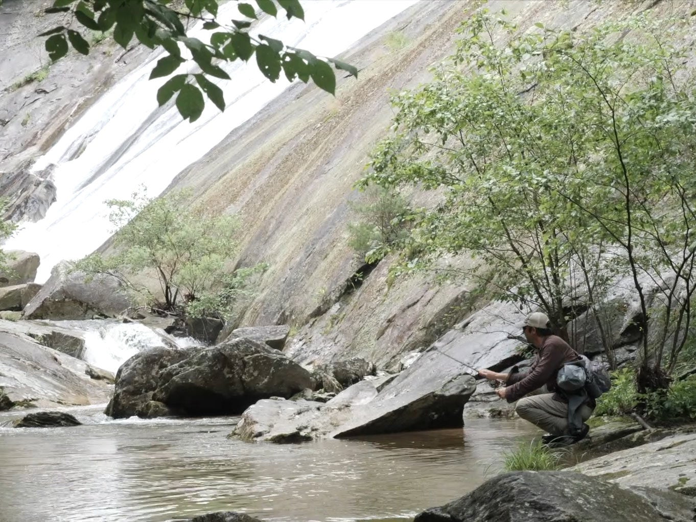 An angler fishing for trout near a waterfall and river.