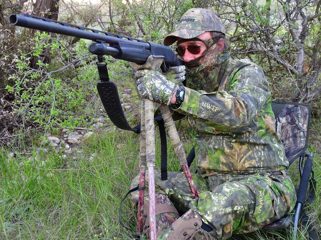 A hunter kneeling in the woods while aiming a shotgun.