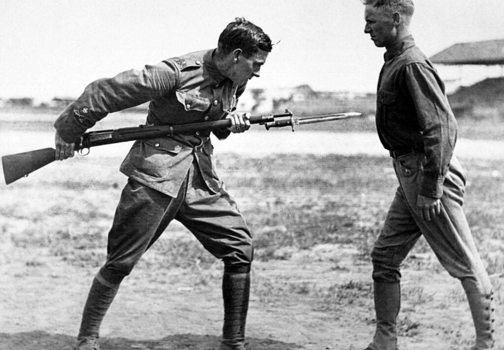 Black and white photograph of two military men training with a bayonet.