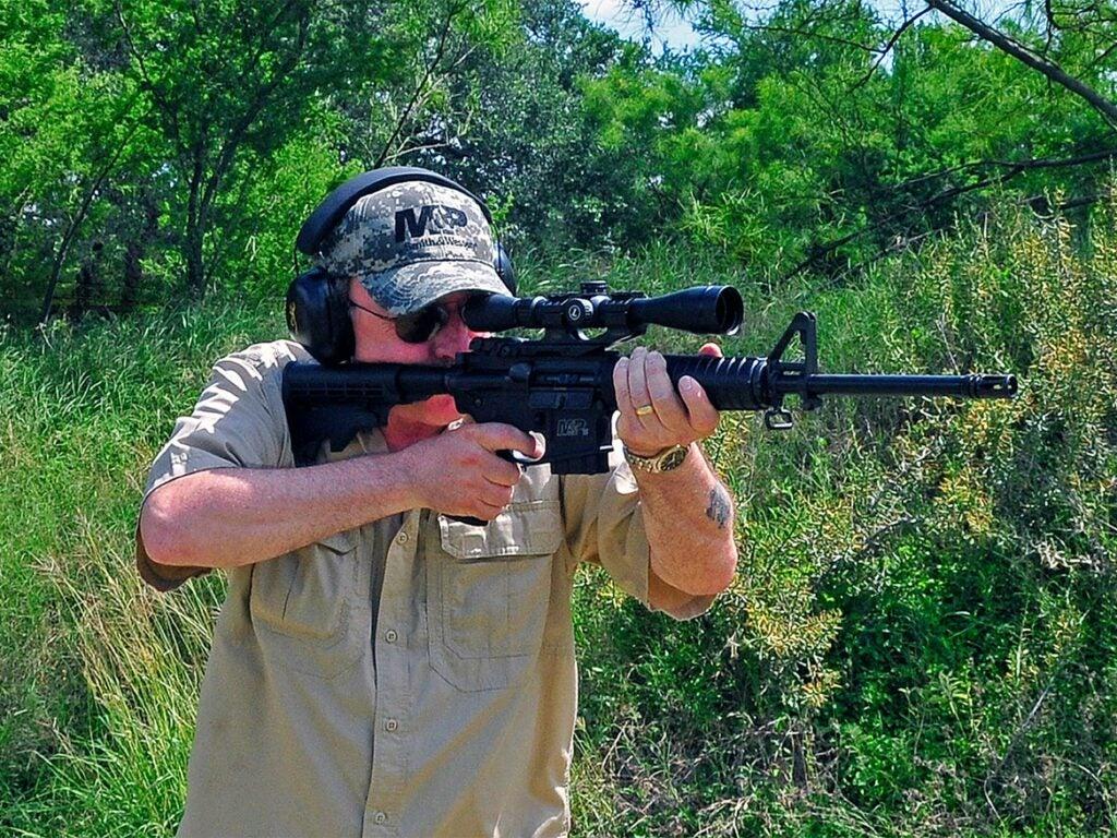 A man aims an AR rifle in the woods.