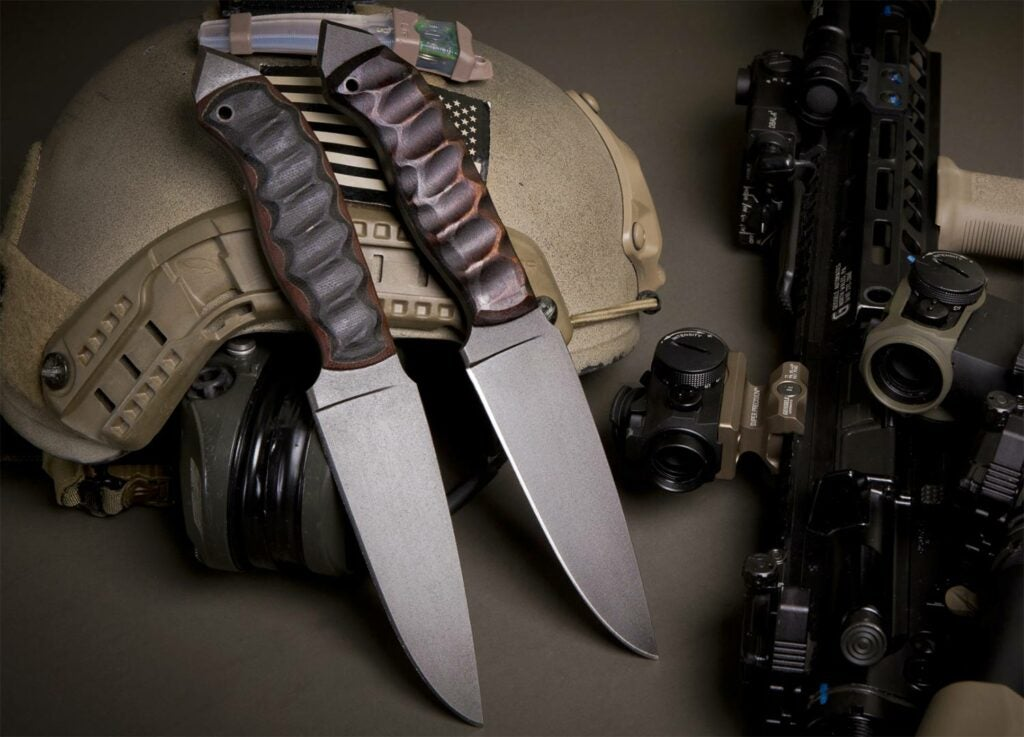 Two bladed winkler knives on a military helmet.