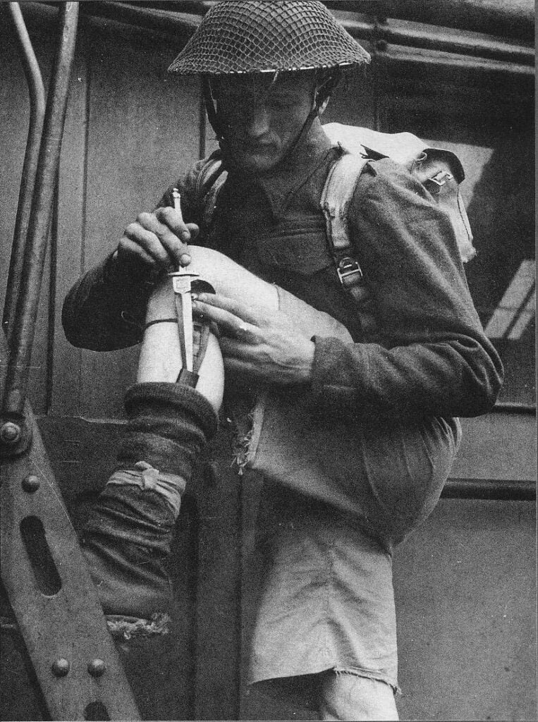 A military officer pulling a knife out of a concealed sheathe.