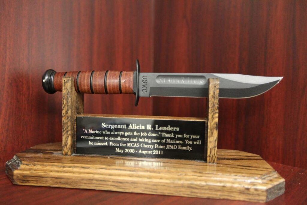 A Kabar fighting knife on a wooden stand and plaque.