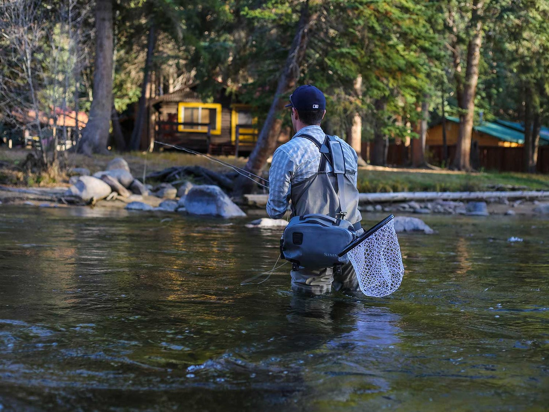 man fishing in a lake in waders