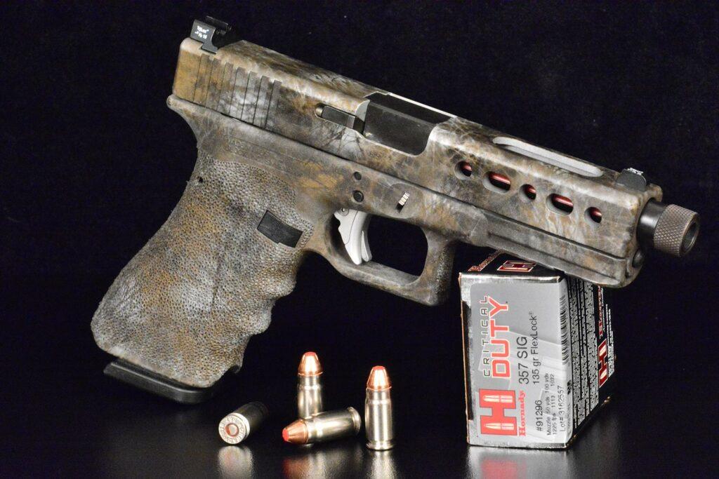 A small camoflauged handgun propped against a box of Hornady ammunition.
