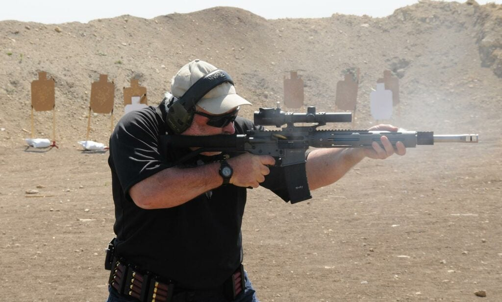 A man wearing ear and eye protection fires a rifle at a shooting range.