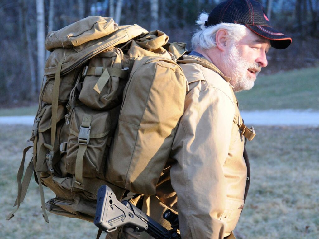 A man wears a backpack packed full of survival materials.