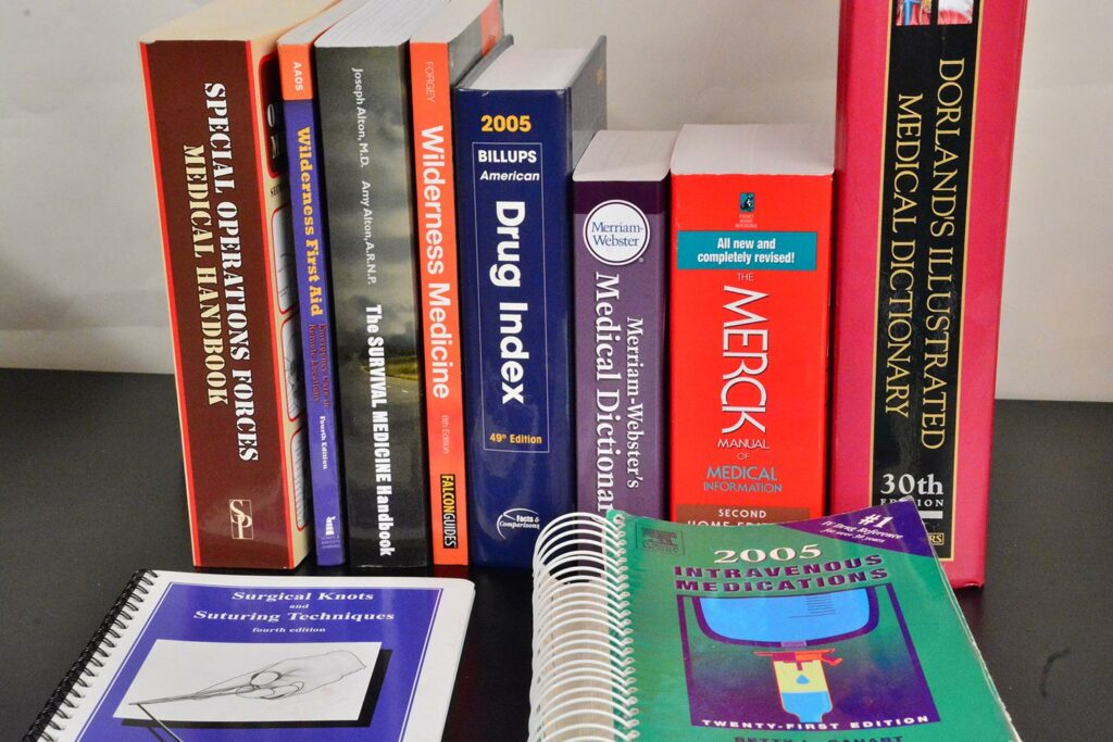 Several survival reference books standing on a table.
