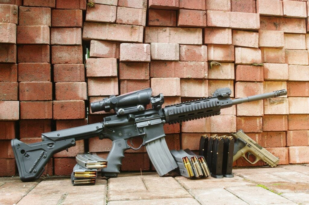 An AR rifle propped up against a pile of bricks.