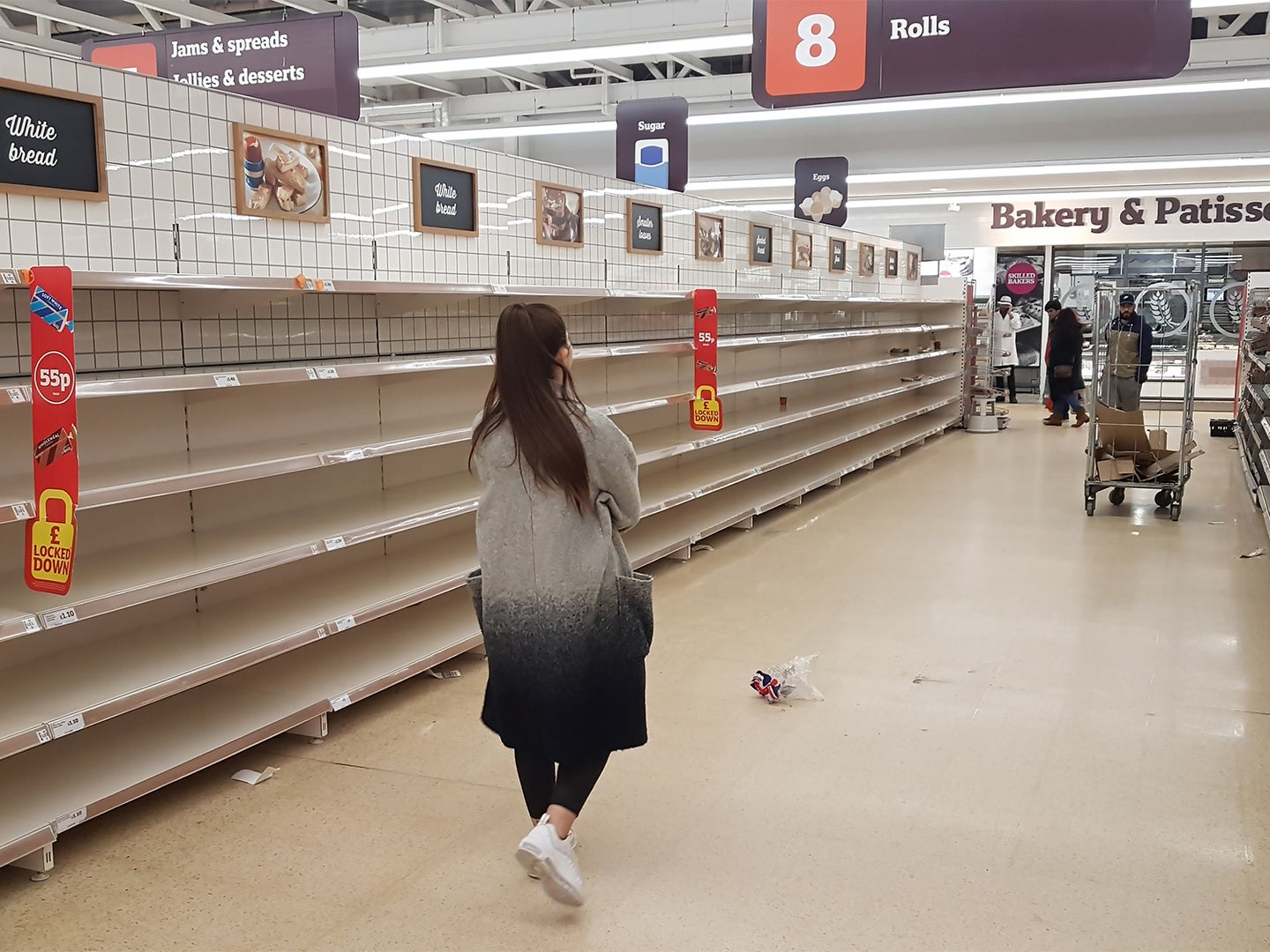 A woman walks through a grocery store aisle with empty shelves.