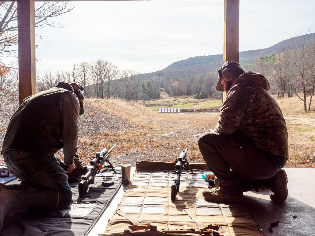 Two shooters readying their precision rifles at the firing line on an outdoor long-range course.