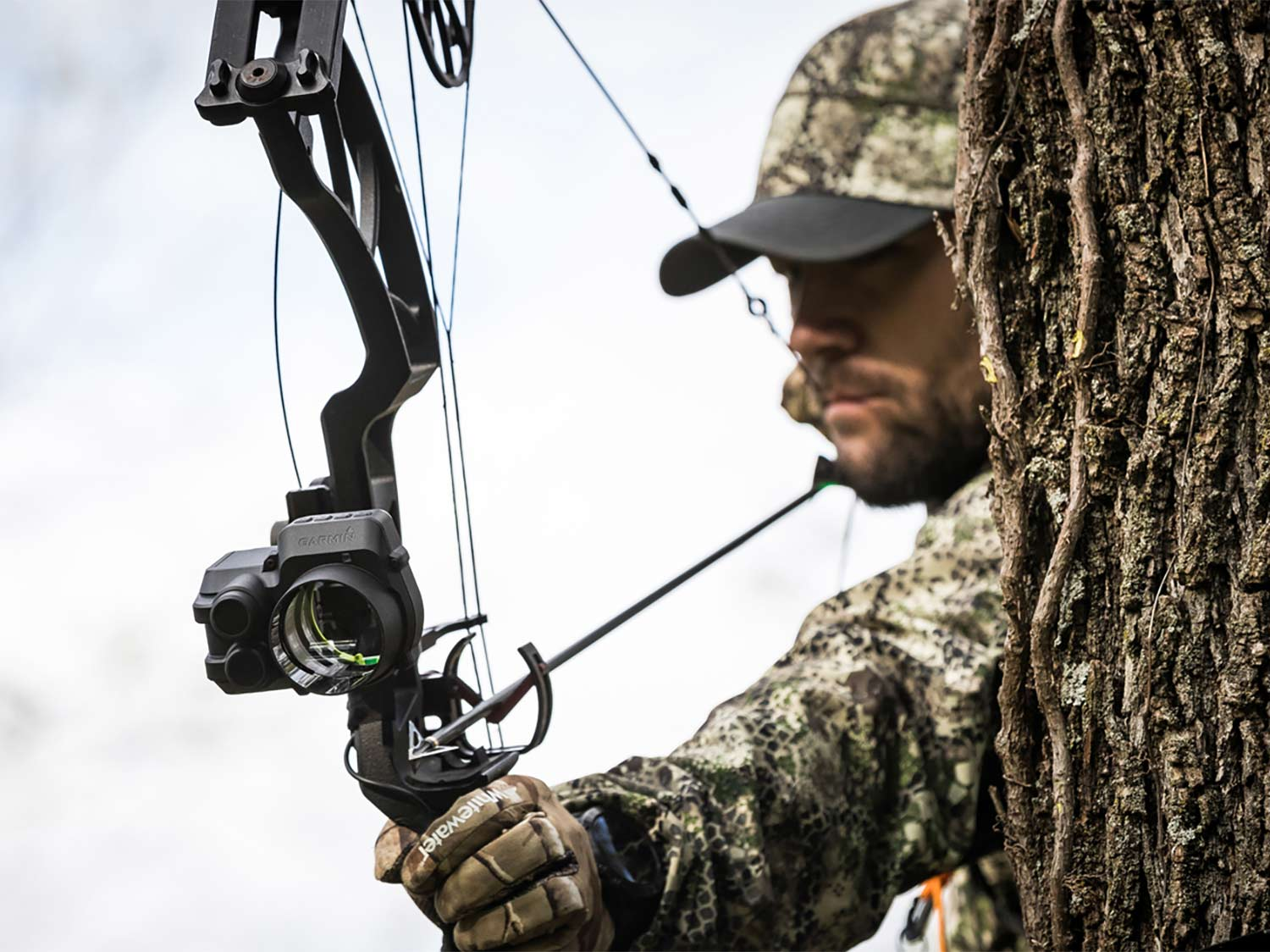 A hunter uses a compound bow fitted with a Garmin bowsight.