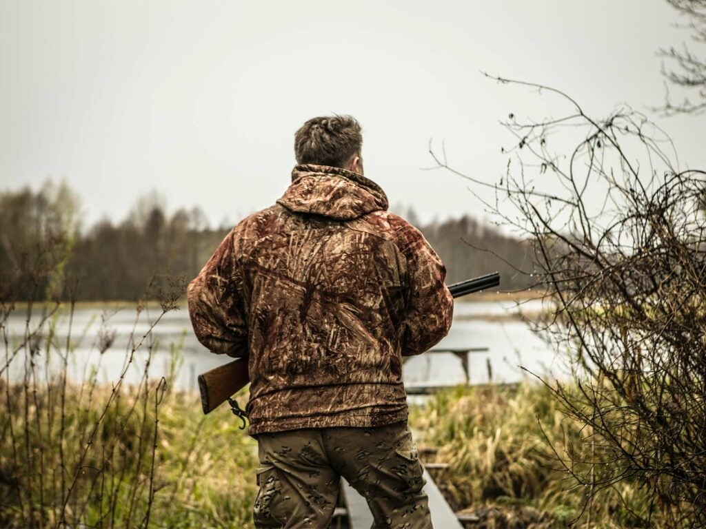 A hunter in camoflauge holds a shotgun while standing near a lake.