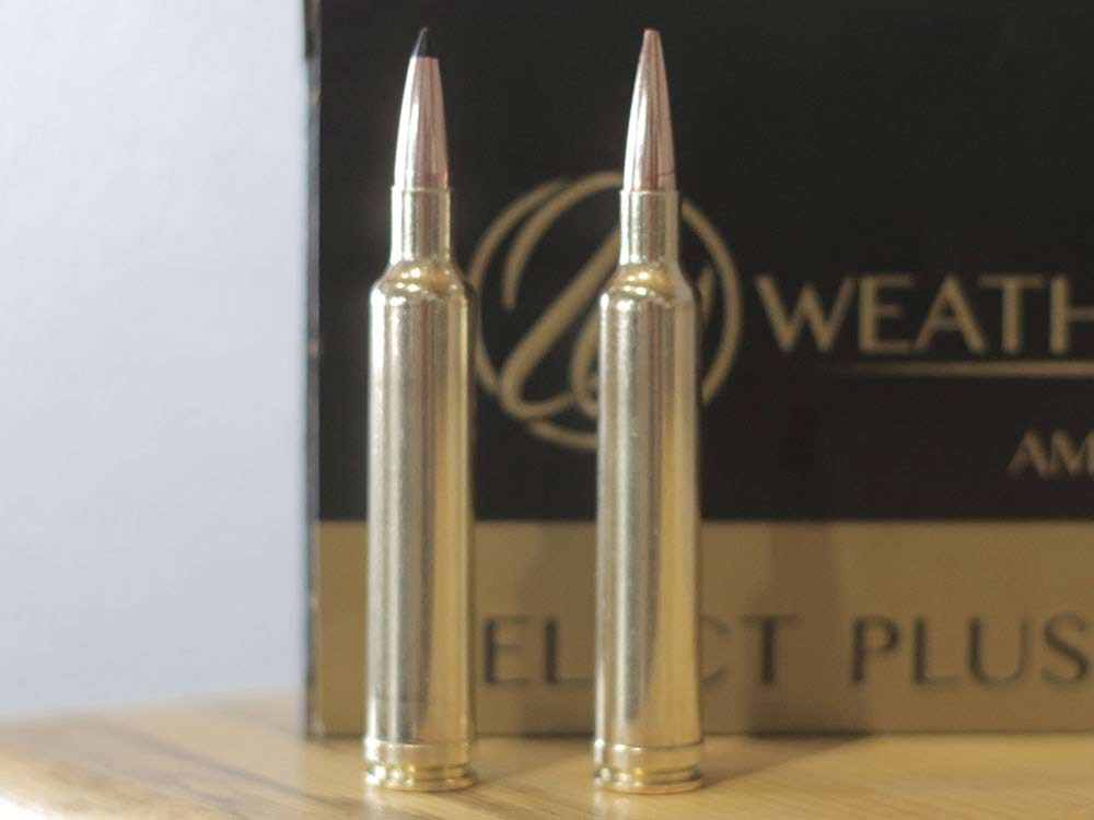 Two brass rifle casings on a table with a box of ammunition in the background.