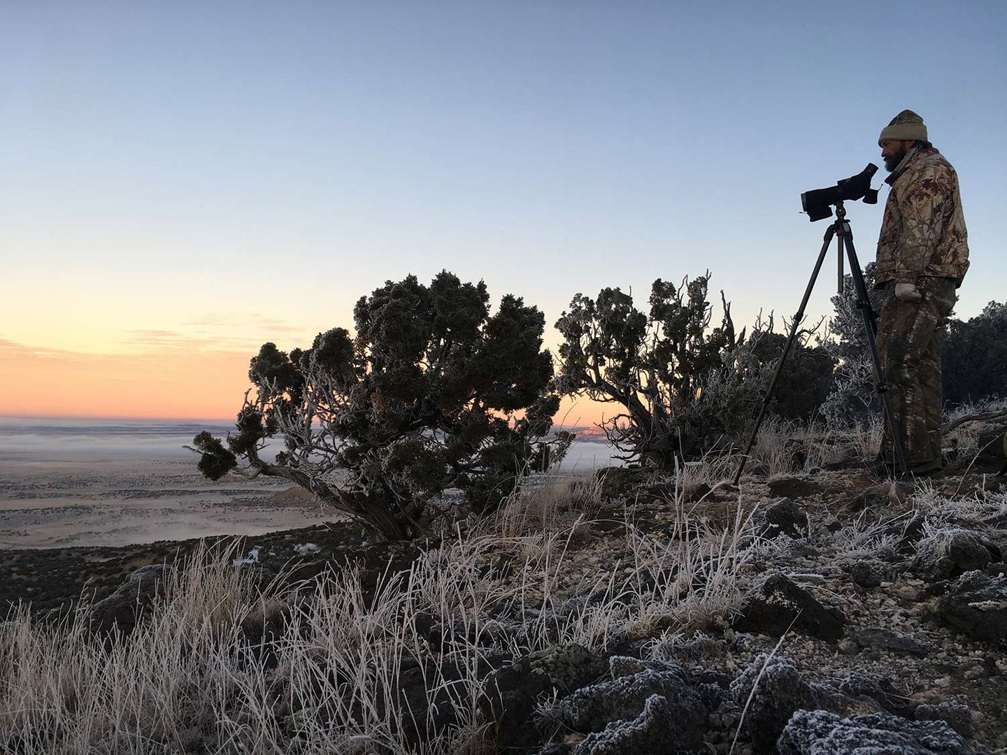 A hunter in camo scouts a western countryside with a spotting scope.