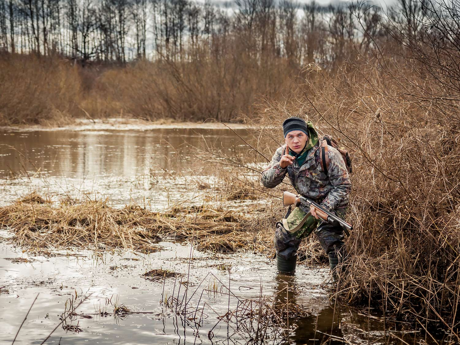 A hunter in camo stands near a brushline on a lake while holding a shotgun.