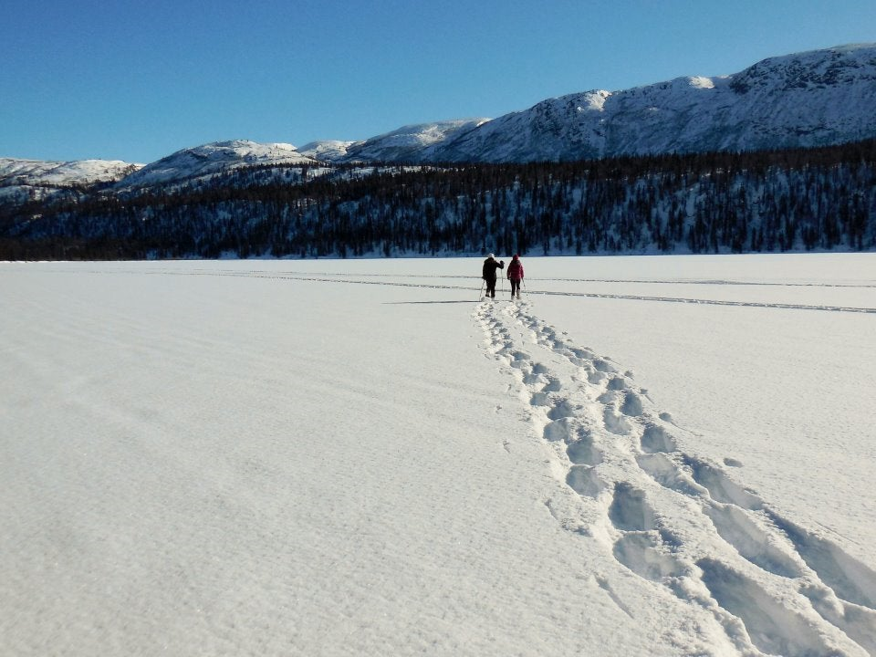 Two men leaving a walking trail in the snow.