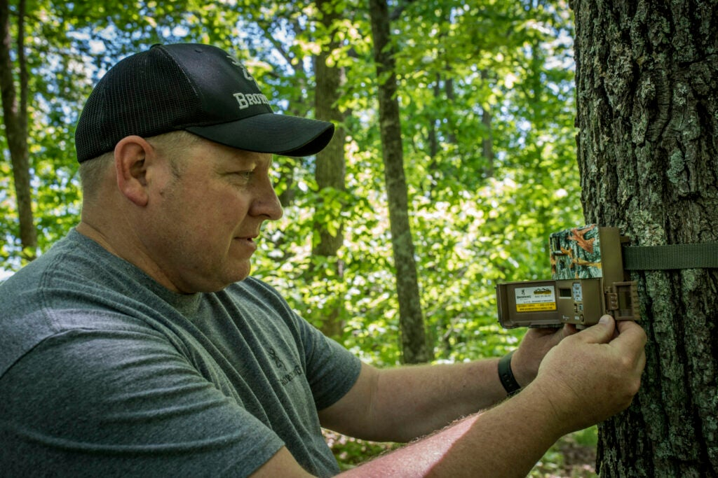 Man operating trail camera in the woods.