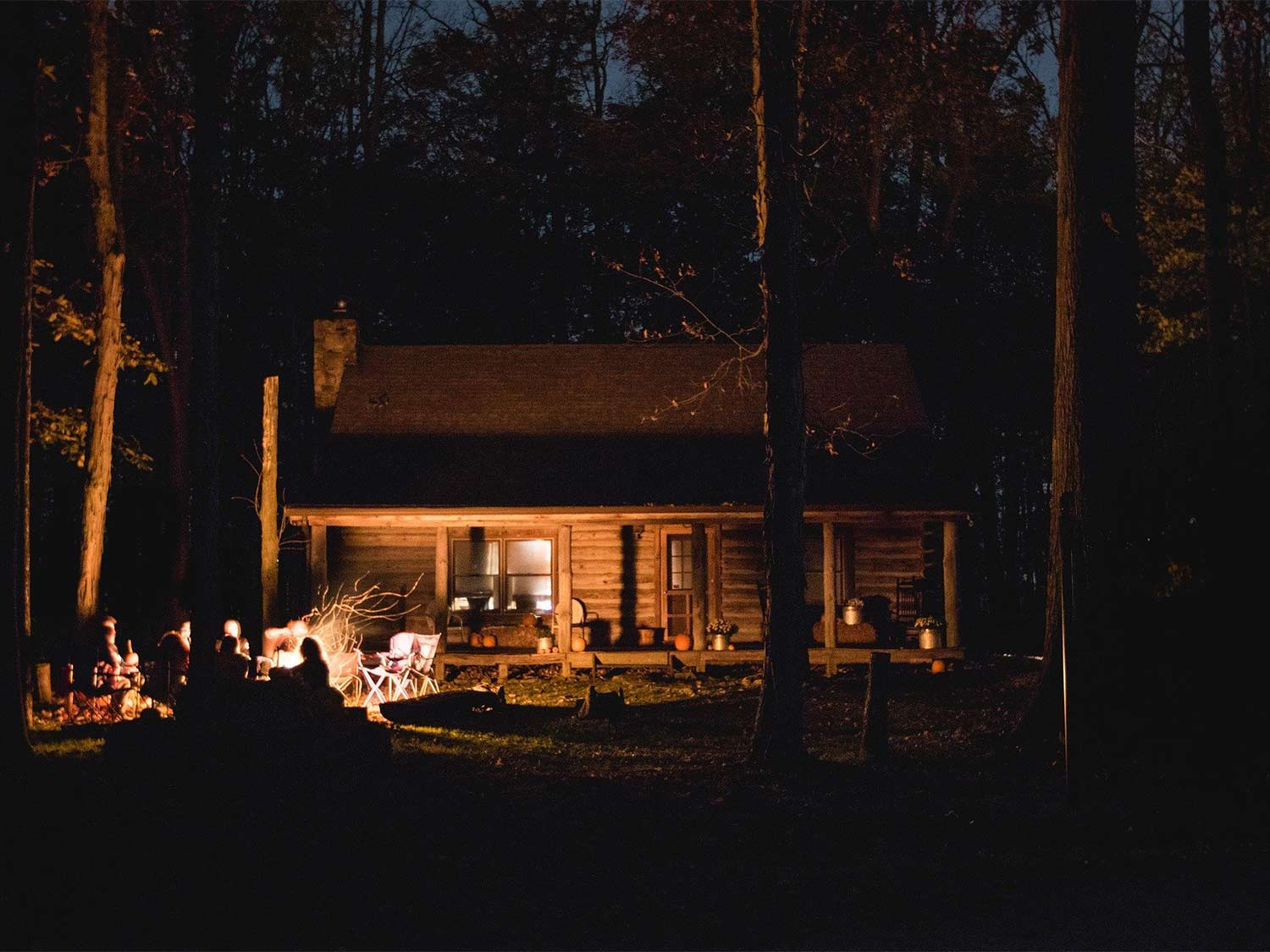Hunters surrounding a campfire at night outside of a hunting cabin in the woods.