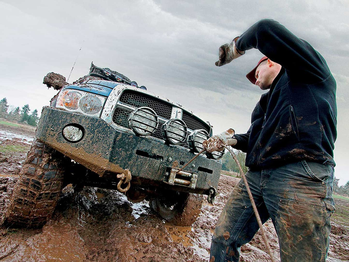 Man using winch with truck.
