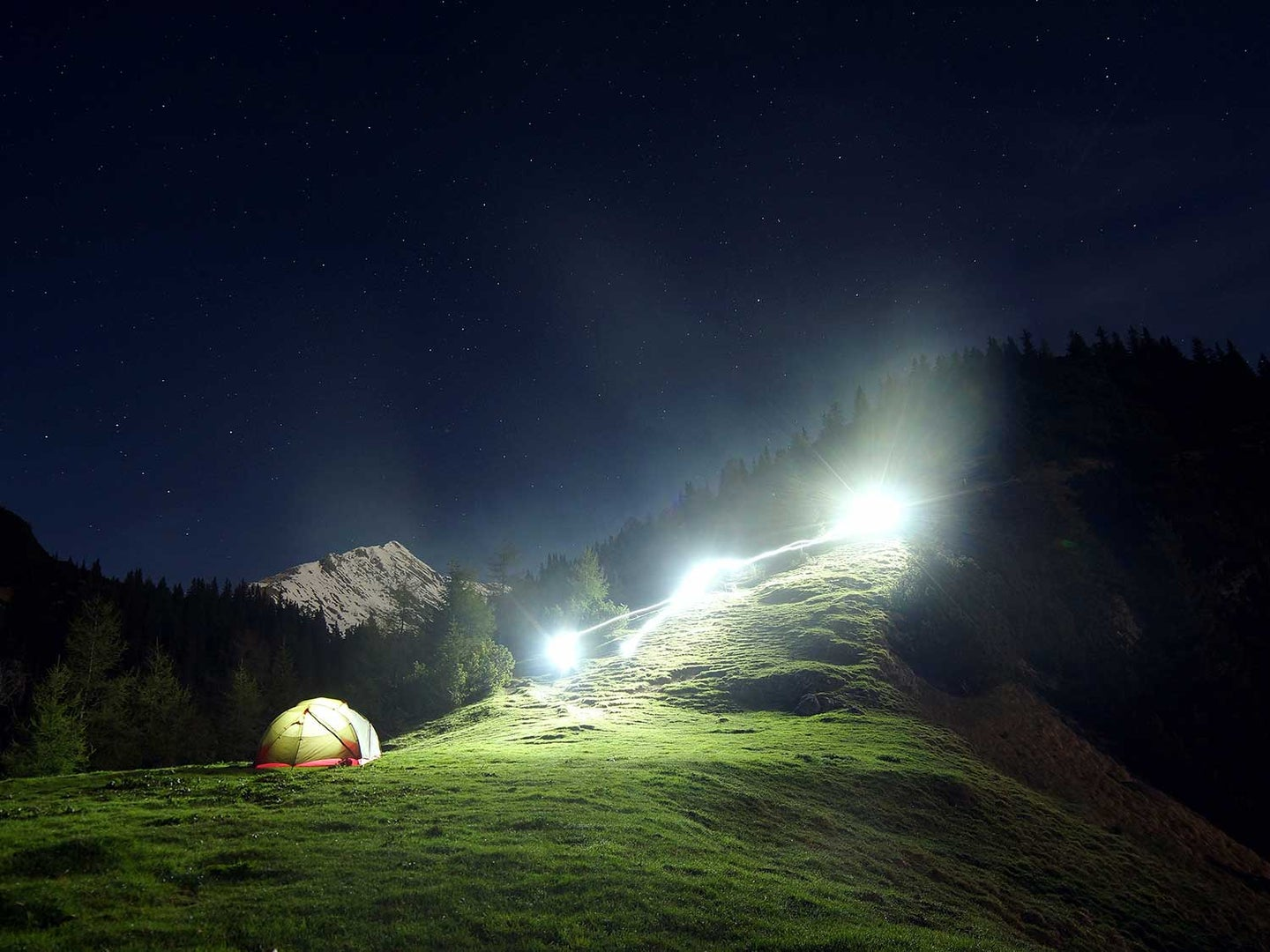 Camping on mountain with lights.