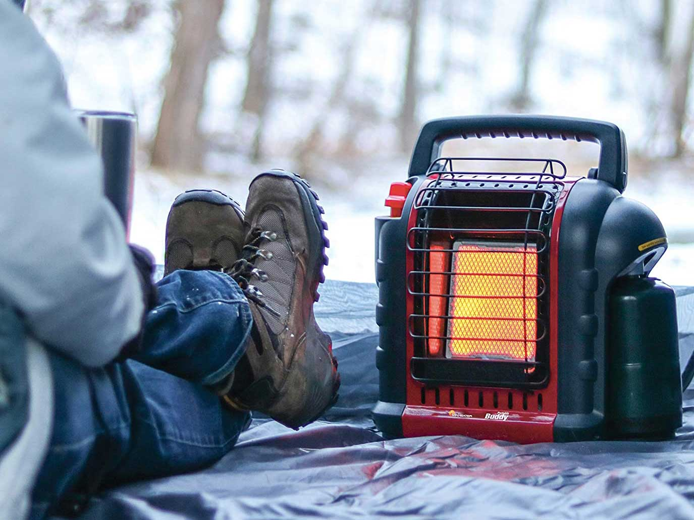 Man using personal heater outdoors in snow.