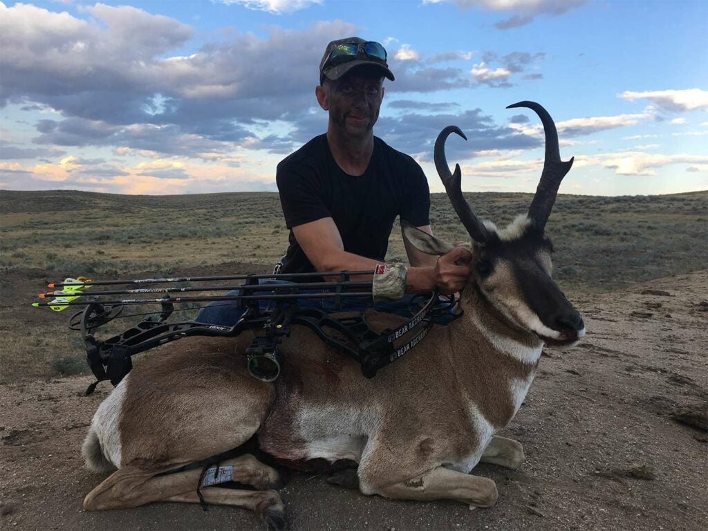A hunter kneeling beside a pronghorn antelope.