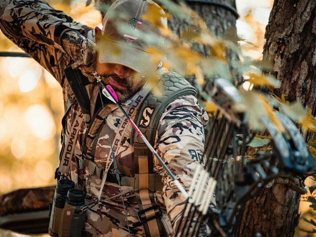 A hunter in full camo draws back on a compound bow while in a tree stand.