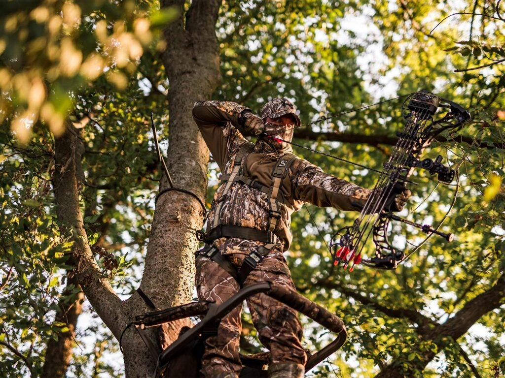 A hunter drawing on a crossbow on a hunt stand in a tree.