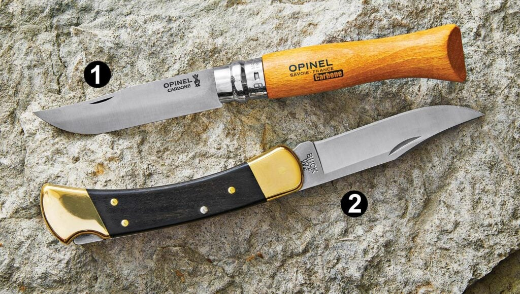 Opinel No. 09 Carbon Steel Folding Knife (top) and the Buck Model 110  Folding Hunter Knife (bottom) resting on a rock.