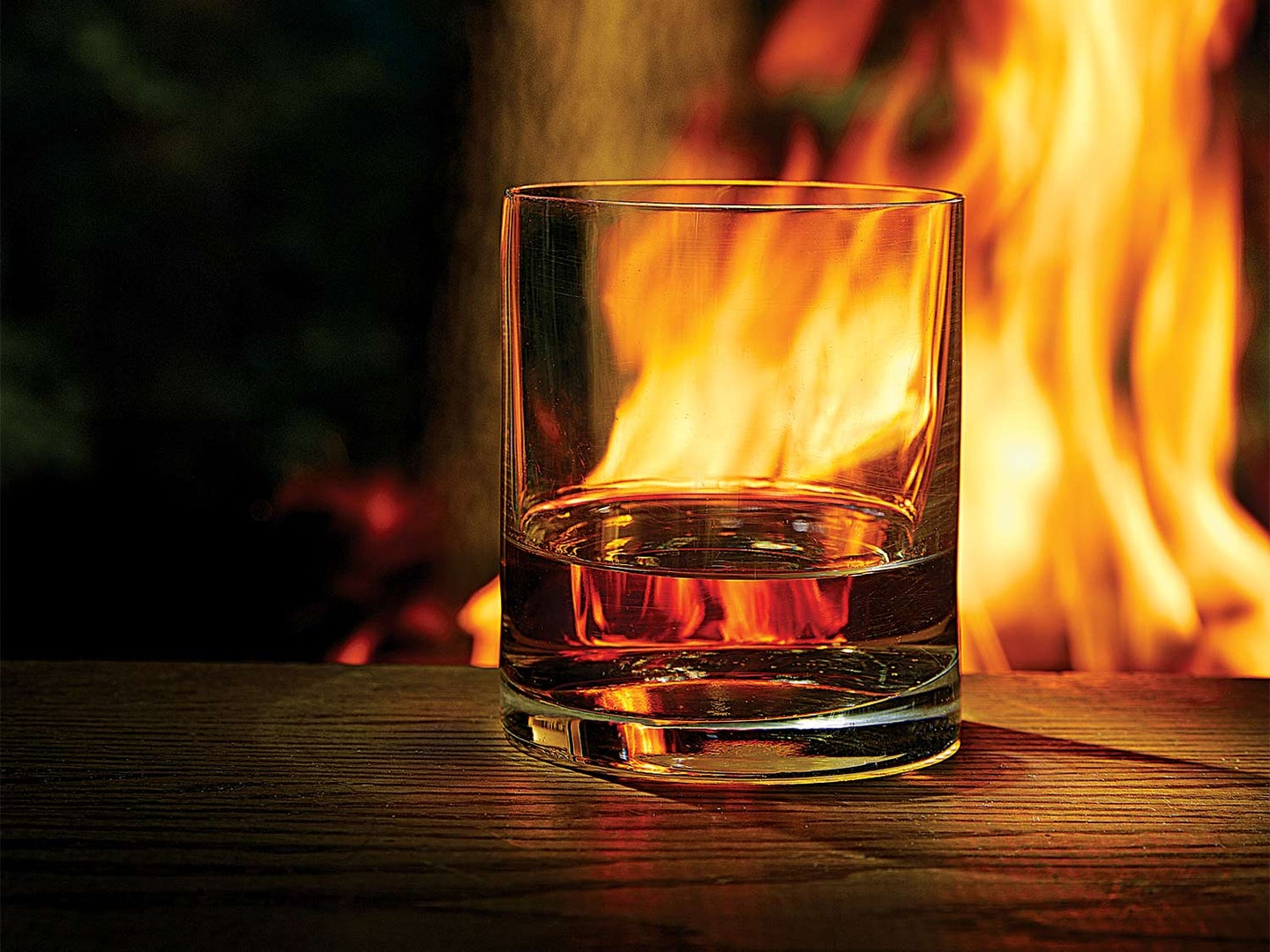 A glass of whiskey at night next to a campfire.