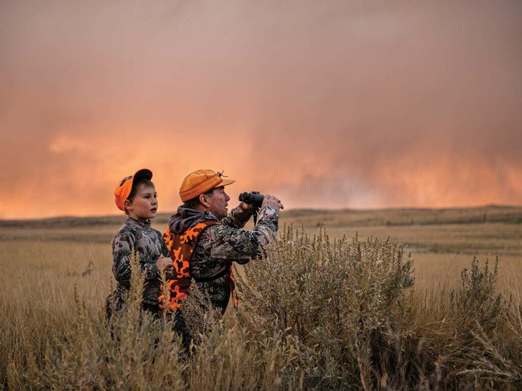 A hunter and small child scouting an open field.
