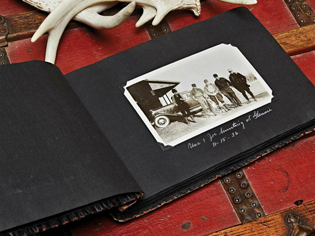 A photo album of vintage photographs on a chest with deer antlers.