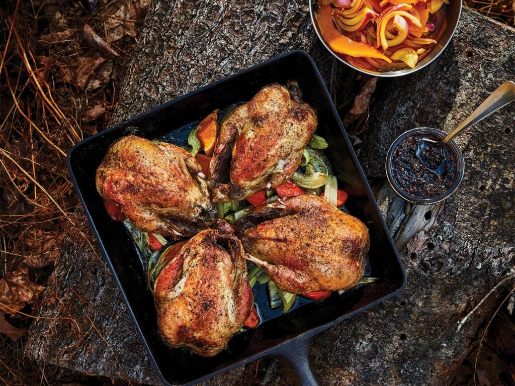Several cooked gamebirds of chukar over vegetables.
