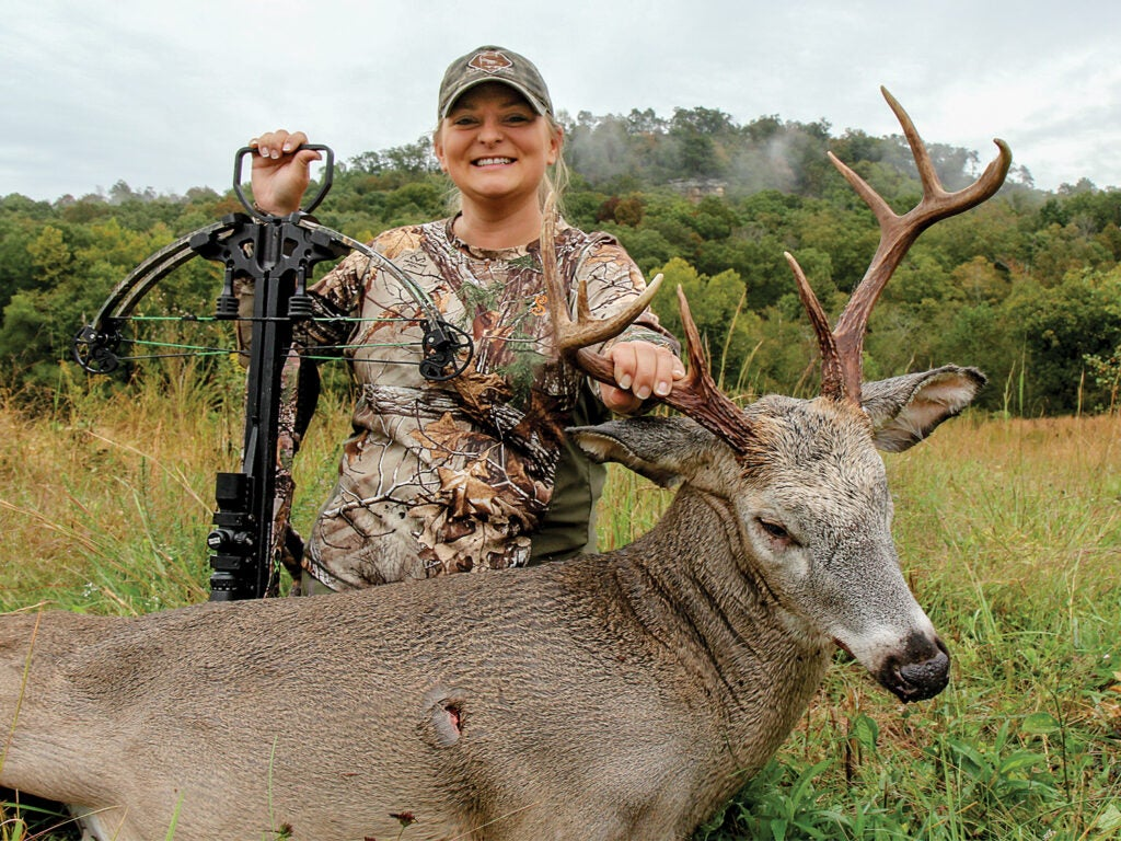 A woman hunter in full camo holds a crossbow while kneeling behind a large buck.