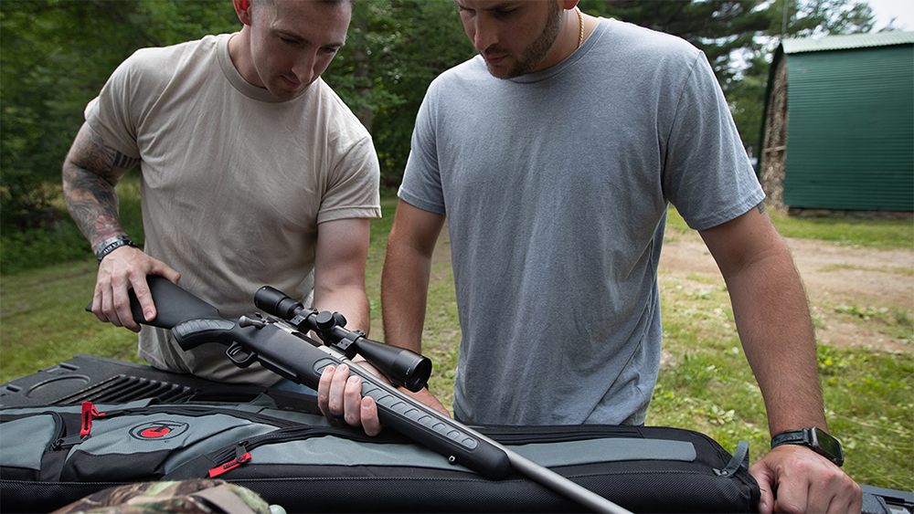 Two men holding a rifle.